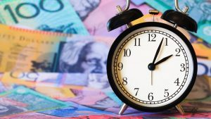 An alarm clock sitting on top of spread out australian bank notes